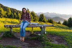 Giovane donna che si siede su una roccia con lo zaino e che guarda all'orizzonte Immagini Stock Libere da Diritti