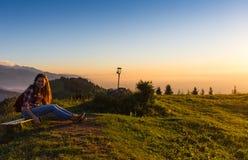Giovane donna che si siede su una roccia con lo zaino e che guarda all'orizzonte Immagine Stock Libera da Diritti