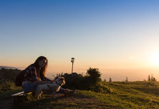 Giovane donna che si siede su una roccia con lo zaino e che guarda all'orizzonte Fotografia Stock Libera da Diritti