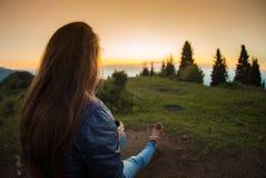 Giovane donna che si siede su una roccia con lo zaino e che guarda all'orizzonte Immagini Stock