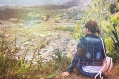 Giovane donna che si siede su una roccia con lo zaino e che guarda all'orizzonte Isola di Bali Vulcano Batur Fotografie Stock