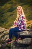 Giovane donna che si siede su una scogliera e che gode di una vista Immagini Stock