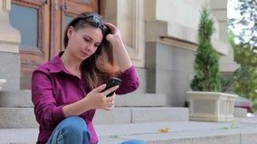 Giovane donna che si siede sui punti e su Internet dei rotoli in suo smartphone archivi video