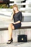 Giovane donna che si siede sul banco e che parla sul telefono cellulare fotografie stock