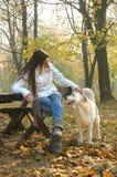 Giovane donna che si siede sul banco nel cane stringente a sé del parco di autunno Fotografie Stock
