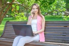 Giovane donna che si siede sul banco in parco che parla sul telefono cellulare e che per mezzo del computer portatile Fotografie Stock