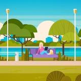 Giovane donna che si siede sul banco in parco facendo uso del computer portatile all'aperto royalty illustrazione gratis