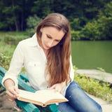 Giovane donna che si siede sul libro di lettura e del banco Immagine Stock