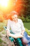 Giovane donna che si siede sul libro di lettura e del banco Fotografia Stock Libera da Diritti