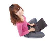 Giovane donna che si siede sul pavimento con un computer portatile Fotografia Stock Libera da Diritti