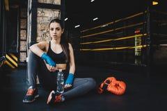 Giovane donna che si siede sul pavimento dopo l'allenamento duro in palestra Fotografia Stock