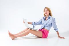 Giovane donna che si siede sul pavimento e che per mezzo del computer portatile Fotografia Stock Libera da Diritti