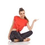 Giovane donna che si siede sul pavimento e sull'indicare Fotografia Stock