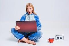 Giovane donna che si siede sul pavimento in suoi pigiami con un computer portatile Fotografia Stock Libera da Diritti