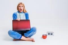 Giovane donna che si siede sul pavimento in suoi pigiami con un computer portatile Immagini Stock Libere da Diritti