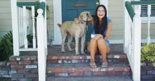 Giovane donna che si siede sul portico con il suo cane Fotografia Stock Libera da Diritti