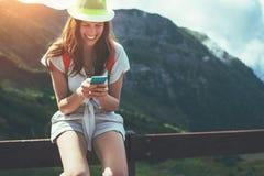 Giovane donna che si siede sul recinto con il telefono cellulare Percorso turistico delle alte montagne al tramonto Mandando un s Fotografia Stock Libera da Diritti