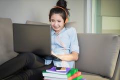 Giovane donna che si siede sul sofà con il computer portatile ed il trasduttore auricolare liste della ragazza Fotografia Stock