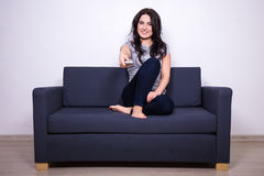 Giovane donna che si siede sul sofà e sulla TV di sorveglianza a casa Immagini Stock
