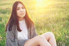 Giovane donna che si siede sull'erba Fotografia Stock Libera da Diritti