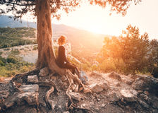 Giovane donna che si siede sulla montagna al tramonto Paesaggio di ESTATE Fotografia Stock