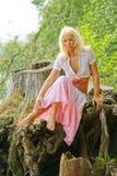 Giovane donna che si siede sulla natura con capelli selvaggi fotografia stock