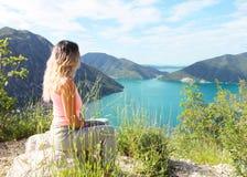 Giovane donna che si siede sulla pietra mentre rilassandosi esaminando bella natura immagine stock