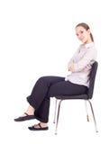 Giovane donna che si siede sulla presidenza nera Fotografia Stock