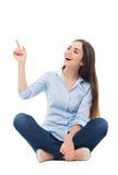 Giovane donna che si siede sulla priorità bassa bianca Fotografie Stock