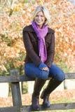 Giovane donna che si siede sulla rete fissa Fotografia Stock