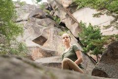 Giovane donna che si siede sulla roccia nella riserva selvaggia Fotografia Stock