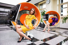Giovane donna che si siede sulla sedia del computer in ufficio Fotografie Stock