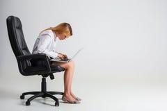 Giovane donna che si siede sulla sedia e che per mezzo del computer portatile Fotografia Stock