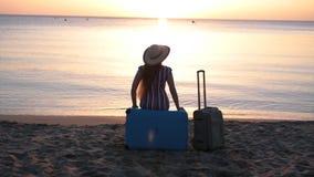 Giovane donna che si siede sulla valigia su una spiaggia video d archivio