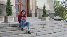 Giovane donna che si siede sulle scale all'entrata alla costruzione e ad esaminare dello smartphone video d archivio