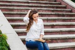 Giovane donna che si siede sulle scale con il libro Immagine Stock Libera da Diritti
