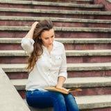 Giovane donna che si siede sulle scale con il libro Fotografia Stock Libera da Diritti