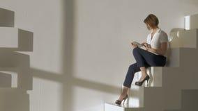 Giovane donna che si siede sulle scale e che per mezzo del computer digitale della compressa stock footage