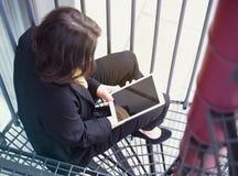 Giovane donna che si siede sulle scale e che tiene libro elettronico Immagini Stock Libere da Diritti