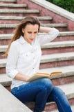 Giovane donna che si siede sulle scale e sul libro di lettura Immagine Stock Libera da Diritti
