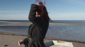 Giovane donna che si siede in una barca sulla spiaggia in tempo soleggiato sul Mar Baltico che balla e che riempie sciocco stock footage