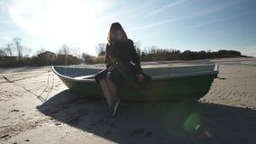 Giovane donna che si siede in una barca sulla spiaggia in tempo soleggiato sul Mar Baltico che balla e che riempie sciocco archivi video