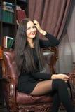 Giovane donna che si siede in una sedia di cuoio Fotografie Stock Libere da Diritti