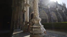 Giovane donna che si siede vicino alle colonne di vecchia costruzione stock footage