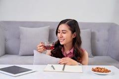 Giovane donna che si siede vicino allo strato a casa ed al caffè bevente Fotografie Stock Libere da Diritti
