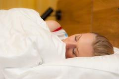Giovane donna che si situa a letto Immagini Stock