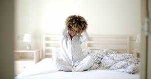 Giovane donna che si sveglia sul letto archivi video