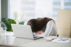 Giovane donna che si trova alla scrivania vicino al computer portatile immagini stock