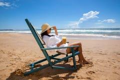 Giovane donna che si trova in cappello di paglia in occhiali da sole sulla spiaggia Fotografia Stock Libera da Diritti