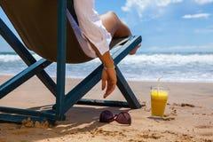 Giovane donna che si trova con gli occhiali da sole ed il succo sulla spiaggia Immagine Stock